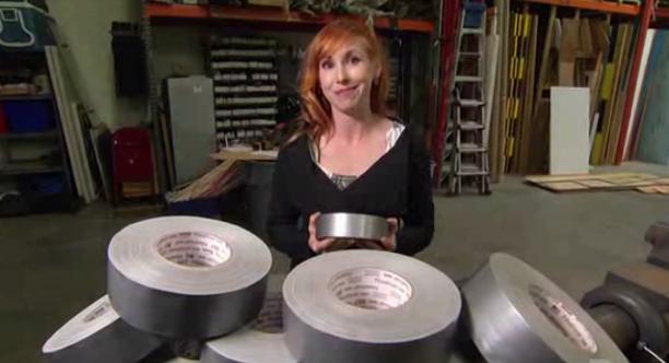Kari Byron från tv-programmet Mythbusters bakom en hög med silvertejp.