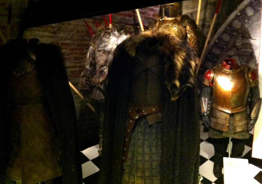 """""""Michele Clapton, kostymdesignern, har haft norra medeltida Europa som förebild för Robb Starks och Ned Starks dräkter (de två längst fram). Men hon betonar att i fantasy gäller inga regler utan man kan plocka fritt från olika platser och århundraden. Dräkterna har också japanska drag med en sorts kjol. Starkätten håller till i norr, vilket hon velat illustrera med de här mörka och murriga färgerna"""", berättar Malin Grundberg. I bakgrunden syns även dräkter och rustningar för Jon Snow, Jamie Lannister och Tyrion Lannister"""