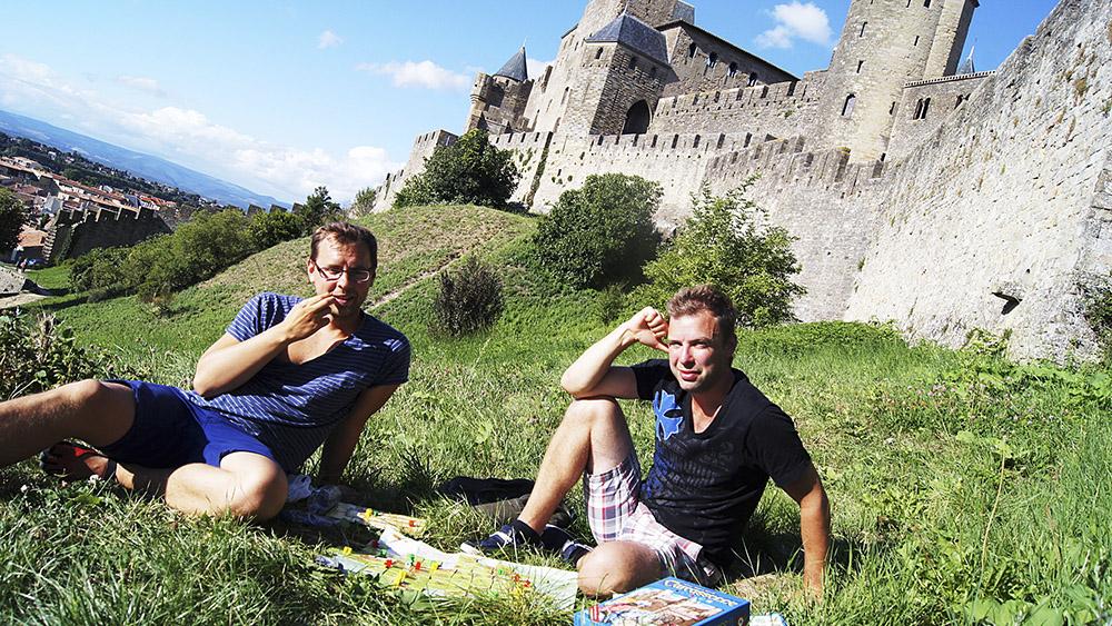 """Efter tre timmar i staden Carcassonne hittade Magnus """"Släpet"""" Anderberg (t.h.) ett Carcassonne–spel och lirade en runda som gubbar på gräset utanför murarna tillsammans med brorsan Erik (t.v.).   Foto: Axel Johnson"""