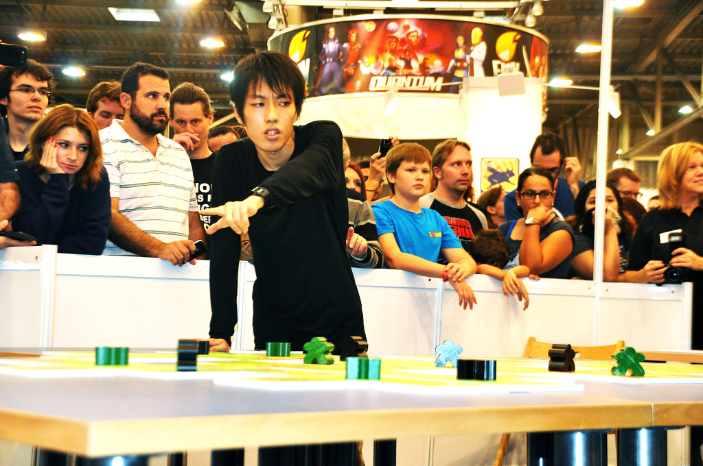 The japanese winner Takafumi Mochiduki at the traditional large finalisttable, with big tiles and meeples.